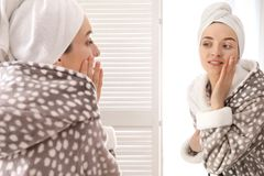 Young woman in bathrobe near mirror at home. Morning routine royalty free stock photos