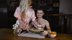Young woman in bathrobe prepared meal for boyfriend. And carries food on tray. Couple is kissing before breakfast and smiling on background of stylish kitchen stock video
