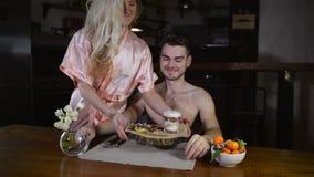 Young woman in bathrobe prepared meal for boyfriend