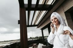 Young woman in bathrobe talking by phone. Concept of relaxation and communication after spa. Waist up low angle portrait of young lady in bathrobe talking by stock images