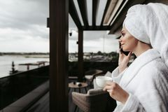 Young woman in bathrobe talking by phone. Concept of relaxation and communication after spa. Waist up side on portrait of young lady in bathrobe talking by phone stock image