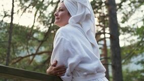 Young woman in a bathrobe and towel on the terrace on a background of mountains and forest. Attractive girl in a