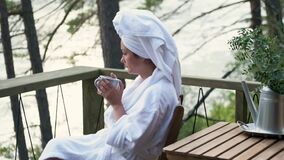 Young woman in a bathrobe and towel on the terrace on a background of mountains and forest. woman with a cup of tea and