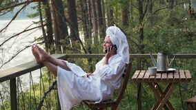 Young woman in a bathrobe and towel on the terrace on the background of mountains and forests talking on the phone