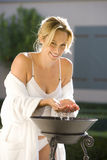 Young woman in bathrobe and underwear washing from basin, smiling, portrait Stock Photo