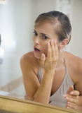 Young woman in bathroom checking skin condition. Concerned young woman in bathroom checking skin condition Stock Image
