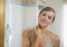 Young woman in bathroom checking skin condition Stock Photo