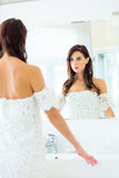 Young woman in bathroom. Photo of the beautiful young woman looking at herself in the mirror in bathroom stock photo