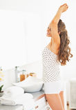 Young woman in bathroom stretching after sleep Stock Photo
