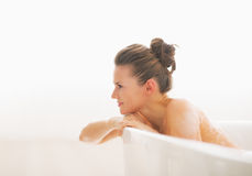Young woman in bathtub looking on copy space Stock Images