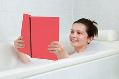 Young woman in bathtub reading book Stock Image