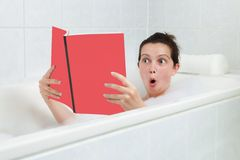 Young woman in bathtub reading book Royalty Free Stock Photography