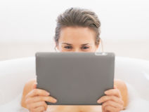 Young woman in bathtub using tablet pc Royalty Free Stock Photography