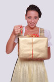 Young woman in Bavarian Dirndl grabs a gift from Royalty Free Stock Photos