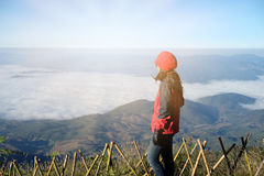 Young woman be dressed in winter set standing on top of mountain Stock Photo