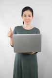 Young woman be pregnant in maternity clothes hold laptop on gray. Cement wall background. concept of excellence sign Stock Image
