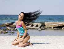 Young woman on the beach. Girl with long hair on the wind Stock Photo