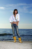 Young woman on the beach. Young beautiful women on the beach in fashion cloths royalty free stock photo