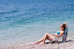 Young woman on a beach. Young woman sitting on a beach chair on a coast Stock Photos