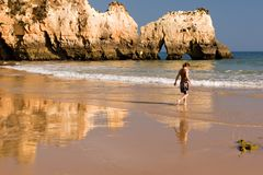 Young woman at the beach. A beautiful young woman walking on the beach at sunset (Algarve, Portugal Royalty Free Stock Photos