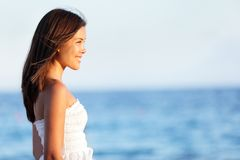 Young woman on beach. Smiling happy at sunset. Lovely sweet asian woman in her twenties enjoying view of ocean standing in white dress Royalty Free Stock Image