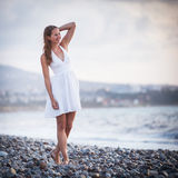 Young woman on the beach. Enjoying a warm summer evening Stock Photography