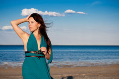 Young woman at the beach. Young woman in a beautiful dress at the beach Royalty Free Stock Image