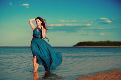 Young woman at the beach. Young woman in a beautiful dress at the beach Stock Photos
