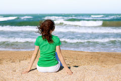 Young woman on the beach. Young woman listening to music with headphones while sitting on the beach and looking at the stormy sea royalty free stock photo