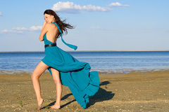 Young woman at the beach. Young woman in a beautiful dress at the beach Royalty Free Stock Images