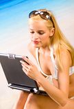 Young woman on the beach. Young beautiful woman in bikini with laptop on sea beach Stock Photos