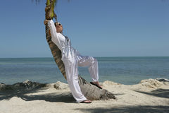 Young Woman on the Beach. A young woman wearing white leaning on a palm tree on the beach Stock Photography