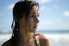 Young woman at the beach. Portrait of a young brunette standing on the beach with wet hair Stock Images