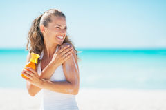 Young woman on beach applying sun block creme. And looking on copy space Royalty Free Stock Image