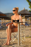 Young woman in a beach bar. The young woman sitting in a beach bar with a bottle of water Royalty Free Stock Images