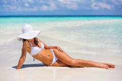 Young woman on the beach. Young woman in bikini relaxing on the beach royalty free stock photos