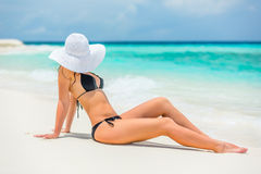 Young woman on the beach. Young woman in bikini sitting on the beach royalty free stock image