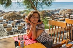Young woman at the beach cafe. The young woman at the beach cafe, she is waiting for Breakfast Royalty Free Stock Images