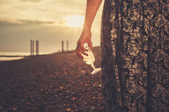 Young woman on the beach with glass of wine. A young woman is on the beach with a glass of wine in her hand as she watches the sunset royalty free stock photos