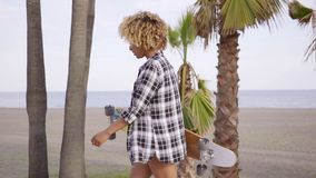 Young woman at the beach with her skateboard stock video