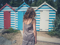 Young woman by beach huts royalty free stock image