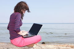 Young woman on the beach with a laptop Royalty Free Stock Photography