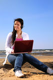 Young woman on the beach with laptop. Sunny day Royalty Free Stock Images