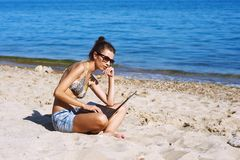 The woman on the beach with laptop. Young woman on beach with laptop .The use of technology on vacation Royalty Free Stock Photography