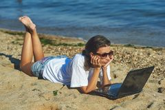 Young woman on beach with laptop. The use of technology on vacation Royalty Free Stock Images