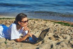 Young woman on beach with laptop. The use of technology on vacation Stock Photo
