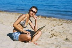 Young woman on beach with laptop . The use of technology on vacation Royalty Free Stock Image