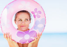 Young woman on beach looking through swim ring on copy space Royalty Free Stock Photography