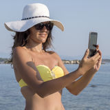 Young woman on beach making selfie Royalty Free Stock Images