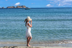 Young woman on the beach overlooking the sea. In the background a motorboat royalty free stock photography